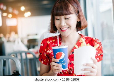 Chiang Mai, Thailand : May 15,2019: Young woman hand holding drink pepsi in restaurant.