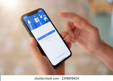 CHIANG MAI, THAILAND - MAY 16, 2019: Facebook social media app logo on log-in, sign-up registration page on mobile app screen on iPhone X (10) in person's hand working on e-commerce shopping business