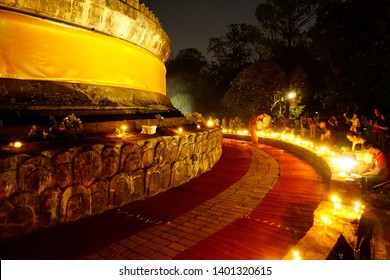 Chiang Mai, Thailand - May 18, 2019: Buddhist ceremony where people walk with lighted candles in hand around ancient pagoda of Wat Umong temple in Vesak Day or Buddha's Birthday or Buddha Day 2019