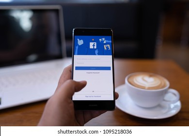 CHIANG MAI, THAILAND - May 19,2018: Man hands holding HUAWEI with facebook app on the screen. Facebook is a popular free social media are used for information sharing and networking.