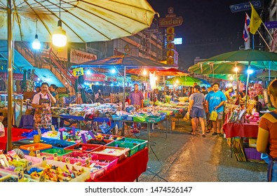 CHIANG MAI, THAILAND - MAY 2, 2019: People walk along the narrow alley among the tiny stalls of Warorot Night Bazaar, on May 2 in Chiang Mai