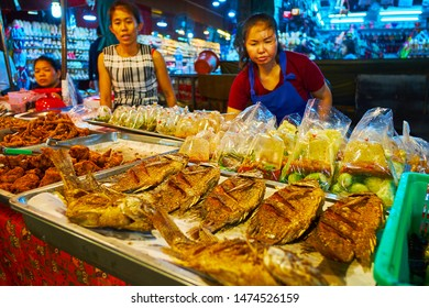 CHIANG MAI, THAILAND - MAY 2, 2019: The stall in Warorot Market offers grilled fish, deep fried chicken and soups in plastic bags, on May 2 in Chiang Mai