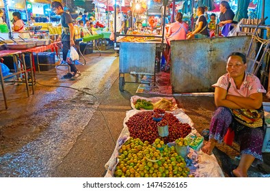 CHIANG MAI, THAILAND - MAY 2, 2019: The vendor is bored, sitting on the floor at the heaps of plums and cherry-plums in Warorot Market, on May 2 in Chiang Mai
