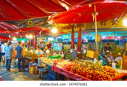 CHIANG MAI, THAILAND - MAY 2, 2019: The fruit stalls of Warorot Night Market with bunches of lychee on branches, apples in plastic bags and heap of durians, on May 2 in Chiang Mai