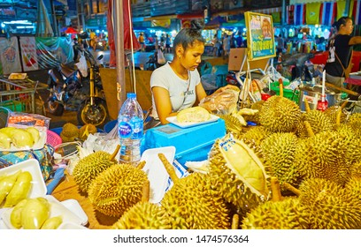 CHIANG MAI, THAILAND - MAY 2, 2019: The street seller of Warorot Night Market cuts and packs durians, standing at the counter of tiny stall, on May 2 in Chiang Mai