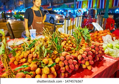 CHIANG MAI, THAILAND - MAY 2, 2019: The big bunches of lychee on branches with leaves in stall of Warorot Night Market, on May 2 in Chiang Mai