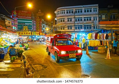 CHIANG MAI, THAILAND - MAY 2, 2019: The songtaew red pickup taxi drives along the street of Warorot Night Market, lined with numerous stalls, on May 2 in Chiang Mai