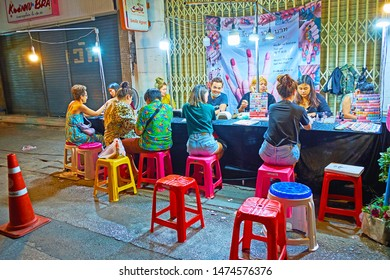CHIANG MAI, THAILAND - MAY 2, 2019: The street nail salon offers manicure service till late night, neighboring with Warorot Night Market, on May 2 in Chiang Mai