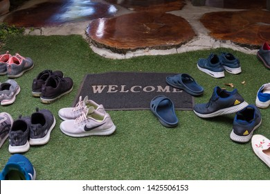 Chiang Mai, Thailand - May 23, 2019 : Various shoe brands on green artificial grass with welcome carpet.