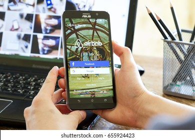 CHIANG MAI, THAILAND - MAY 24, 2016: man hand holding Asus Zenfone 2 mobile phone with screen shot of Airbnb application. Airbnb is a website for people to list, find, and rent lodging.