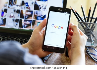 CHIANG MAI, THAILAND - MAY 24, 2016: man hand holding Asus Zenfone 2 mobile phone with screen shot of Google Chrome application. Google Chrome is a freeware web browser developed by Google