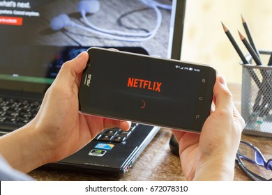 CHIANG MAI, THAILAND - MAY 24, 2016: man hand holding Asus Zenfone 2 mobile phone with screen shot of Netflix application. Netflix is a global provider of streaming movies and TV series.