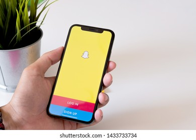 CHIANG MAI ,THAILAND MAY 6 2019 : Man holding a iPhone Xs with social network service Snapchat on the screen. iPhone Xs was created and developed by the Apple inc. Snapchat application on iPhone Xs