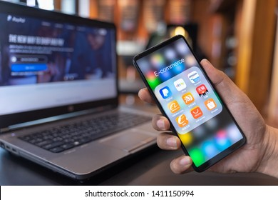 CHIANG MAI, THAILAND - May.01,2019: Man holding Xiaomi Mi Mix 3 with icons of E-commerce and online shopping on screen.smartphone lifestyle,e-commerce app concept.