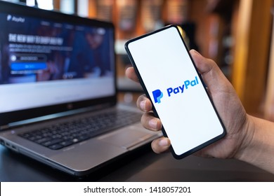 CHIANG MAI, THAILAND - May.01,2019: Man holding Xiaomi Mi Mix 3 with PayPal apps on the screen. PayPal is an online electronic payment system.