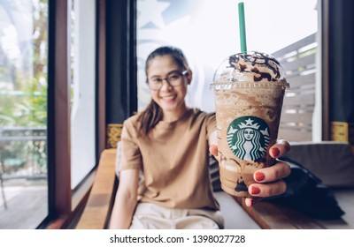 Chiang Mai, Thailand : May-15-2019 : Asian woman holding a cup of Triple mocha frappuccino in Starbucks coffee shop. One of popular drinks menu of Starbucks coffee.
