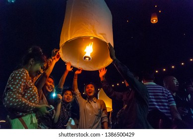 Chiang Mai, Thailand - Nov 2015: Group of friends lightning up a lantern to release it during Loy Krathong festival in Chiang Mai