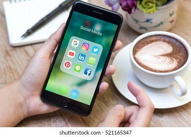 CHIANG MAI, THAILAND - NOVEMBER 14th, 2016: Hands using Iphone7 Plus jet black color with icons of social media on screen with latte art, smartphone life style, smartphone era, smartphone in everyday