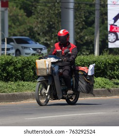 CHIANG MAI, THAILAND -NOVEMBER  16 2017: Postman and Motercycle of Thailand Post. Photo at road no.121 about 8 km from downtown Chiangmai, thailand.