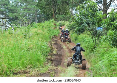 CHIANG MAI, THAILAND - NOVEMBER 23 : Tourists riding ATV to nature adventure on dirt track on NOVEMBER 23, 2013 in Chiang Mai, Thailand.
