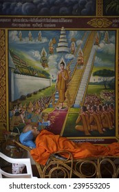 CHIANG MAI, THAILAND - NOVEMBER 5, 2014: Buddhist monk lies resting under religious artwork at the entrance to a temple.