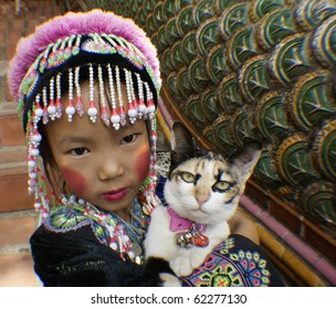 CHIANG MAI, THAILAND- NOVEMBER 9:An unidentified  girl embraces her cat on the steps of the Doi Suthep temple in Chiang Mai, Thailand on November 9, 2009. The temple is a famous tourist destination.