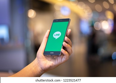 CHIANG MAI, THAILAND - Oct. 28,2018: Man holding HUAWEI with LINE apps on screen. LINE is a new communication app which allows you to make free voice calls and send free messages.