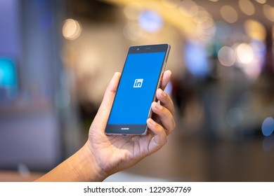CHIANG MAI, THAILAND - Oct. 28,2018: Man holding HUAWEI mobile phone with Linkedin application on the screen. Linkedin is a business and employment oriented social networking service.