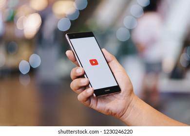 CHIANG MAI, THAILAND - Oct. 28,2018: Man holding HUAWEI with Youtube apps on screen. YouTube is the popular online video sharing website.