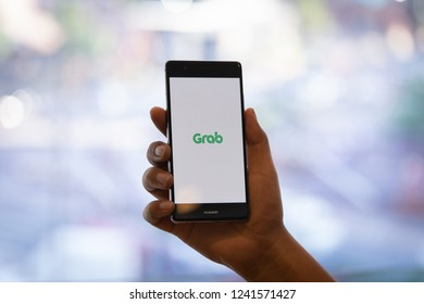 CHIANG MAI, THAILAND - Oct. 28,2018: Man holding HUAWEI with Grab apps on screen. Grab is smartphone app all-in-one transport booking in South-East Asia.