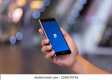 CHIANG MAI, THAILAND - Oct. 28,2018: Man holding HUAWEI with PayPal apps on the screen. PayPal is an online electronic payment system.