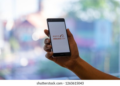 CHIANG MAI, THAILAND - Oct. 28,2018: Man holding HUAWEI with alibaba apps on screen. Alibaba's the the world's biggest online commerce company. It's three main sites Taobao,Tmall and Alibaba.