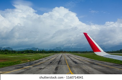 Chiang Mai, Thailand - Oct 5, 2017. Airport runway with airplane wing in sunny day.