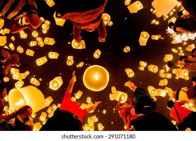 CHIANG MAI, THAILAND - OCTOBER 20, 2010: Group of Thai people launch a sky lantern on the night of the annual festival known as Yee Peng (Yi Peng).