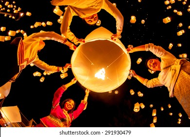 CHIANG MAI, THAILAND - OCTOBER 24, 2009: Group of Thai people launch a sky lantern on the night of the annual festival known as Yee Peng (Yi Peng).