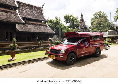 CHIANG MAI, THAILAND - OCTOBER 7: Iconic traditional red truck taxi parked and waiting for the passenger  at  Wat Lok Moli in Chiang Mai, Thailand