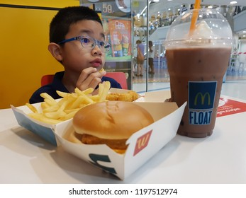 CHIANG MAI, THAILAND - OCTOBER 8: 2018 image of unrecognized asian boy eating hamburger in Mcdonald shop at Central airport plaza near McCafe shop sell fast food and drinks near Hangdong street.