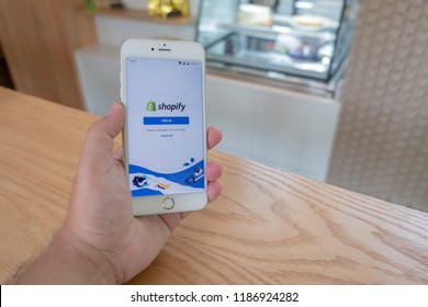 Chiang Mai / Thailand - September 22 2018 :A man sit in cafe holding mobile with shopify screen