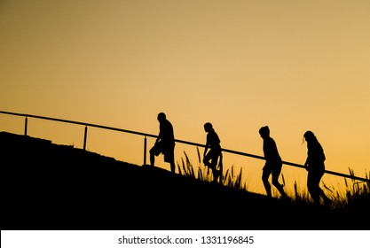 Chiang Mai, THAILAND-December 31, 2018: Silhouette image of caucasian family of four people, father, daughters and mother walking up the hill at RAJAPRUK ROYAL PARK with twilight sky background.
