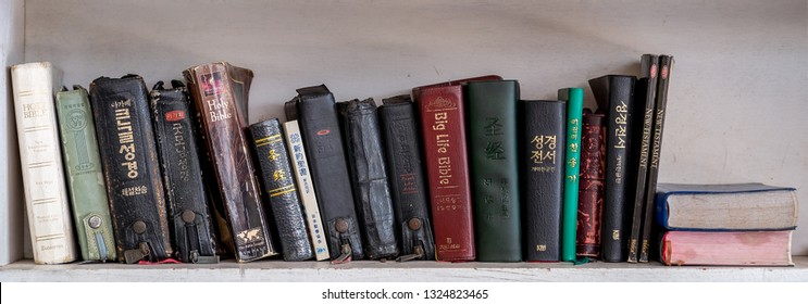 CHIANG MAI, THAILNAD - 24 JANUARY 2019 :  Numerous Holy Bibles sit in a row on wooden shelf. Bookshelf with used prayer books inside.