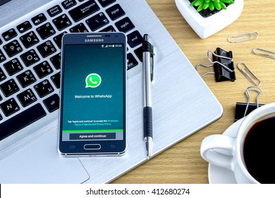 CHIANG MAI,THAILAND - APRIL 29, 2016 : Samsung galaxy Alpha with whatsapp app on the screen lying on wood desk office. Top view of Business work place.