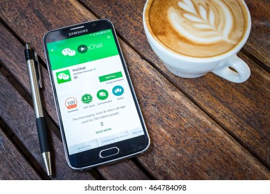 CHIANG MAI,THAILAND - AUG 7, 2016 : Asian Woman holding Samsung Galaxy S6 with wechat app on the screen on Wood desk office. Top view of Business workplace.