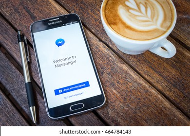 CHIANG MAI,THAILAND - AUG 7, 2016 : Asian Woman holding Samsung Galaxy S6 with facebook messenger app on the screen on Wood desk office. Top view of Business workplace.