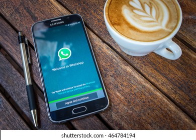 CHIANG MAI,THAILAND - AUG 7, 2016 : Asian Woman holding Samsung Galaxy S6 with whatsapp app on the screen on Wood desk office. Top view of Business workplace.