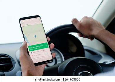 CHIANG MAI,THAILAND - August 26, 2018 : Samsung galaxy S8 Plus open grab application on man hands in car,Grab taxi Many Thailand people are attracted to join the ride sharing services business.