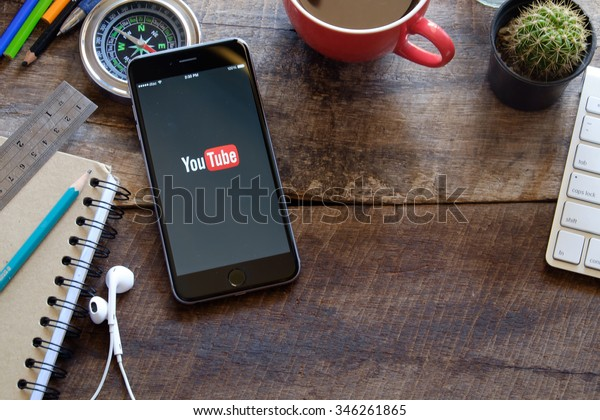 CHIANG MAI,THAILAND, DEC 02 2015 : Brand new Apple iPhone 6 plus with YouTube app on the screen lying on old wood desk with headphones. YouTube is the popular online video sharing website
