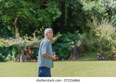 Chiang Mai,Thailand -Dec 06, 2015: Unidentified old man walking on grass at Chiang Mai Chiang Mai Province, Thailand