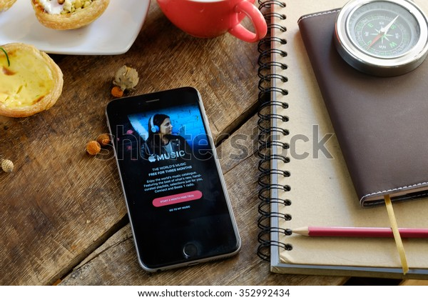 CHIANG MAI,THAILAND - DEC 14,2015 : A man hand holding screen Apple music app showing on iPhone 6 plus in his office. Apple Music is the new iTunes-based music streaming service that arrived on iPhone