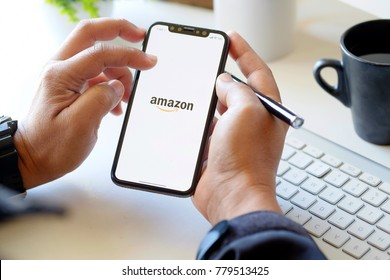 CHIANG MAI,THAILAND - DEC 22, 2017 : iPhone X showing Amazon logo and credit card shopping online in man hands. Amazon.com, Inc. American international electronic commerce company.