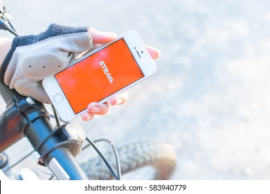 CHIANG MAI,THAILAND - FEBURARY 18,2017:A woman wear gloves and holding a smartphone with logo of Strava application.Strava is the most popular for people who love to riding a bicycle.